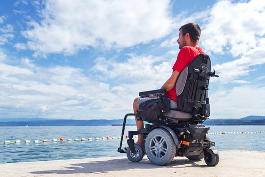 Man with muscular dystrophy on electric wheelchair outdoors looking at sea.