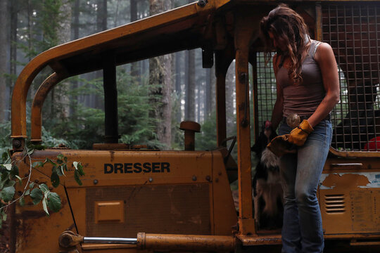 Nicole West, part of the Hillbilly Brigade of some 1,200 men and women who spontaneously came together to fight fires, pets her dog Oink on a bulldozer during the aftermath of the Riverside Fire near Molalla, Oregon