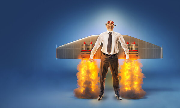 businessman with wings and flares on his back with flames and smoke.