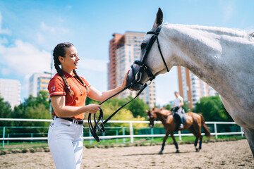 Happy female jockey enjoying free time for summer dressage in paddock of country club take care of animal friend, carefree Caucasian woman pat champion stallion during break from horseback training