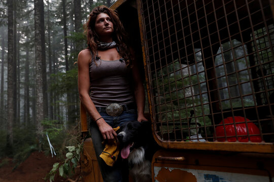 Nicole West, part of the Hillbilly Brigade of some 1,200 men and women who spontaneously came together to fight fires, stands for a portrait petting her dog Oink on a bulldozer during the aftermath of the Riverside Fire near Molalla, Oregon