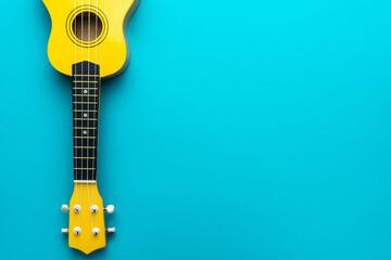 Minimalist photo of ukulele with copy space. Yellow colored wooden ukulele guitar on the turquoise blue background.