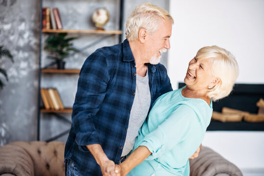 Portrait of modern romantic elderly couple is hugging, embracing gently, dancing at home. Senior spouses stand holding hands, looks to each other and laugh happily