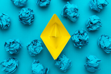 New idea concept with crumpled office paper and yellow paper ship. Top view of great business idea concept over blue background with yellow paper boat in the center.