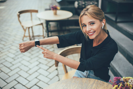 Portrait of cheerful Caucasian woman in electronic headphones showing touchscreen of wearable smartwatch during promotion photo session in sidewalk cafeteria, happy girl in earbuds smiling at camera
