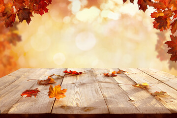 Sunlight in autumn forest. Beautiful  landscape with yellow trees and sun. Colorful  foliage on wooden table. Falling  leaves natural background.