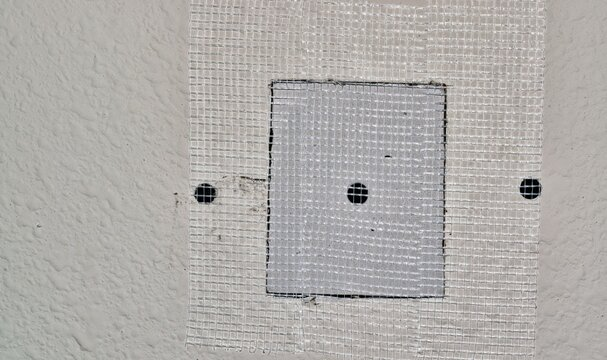 Drywall repairs in wall, fiberglass tape covering a square repair panel screwed in for support. Copy space on the left side of image. Repair, DIY home maintenance, step by step.