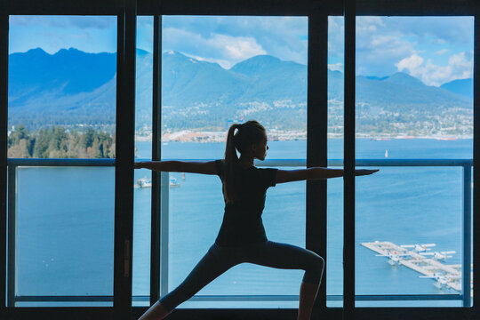 Yoga class in hotel fitness gym room. Scenic view of nature and mountains from Vancouver, Canada. Luxury healthy active living.