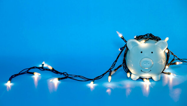 Blue piggy bank with Christmas string lights on happy December festival, Enjoy savings for spending money on the holiday's concept