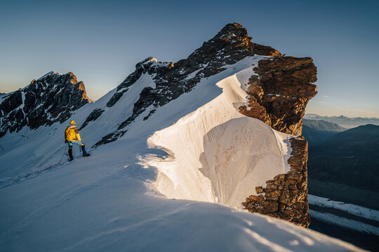 An alpinist climbing a rocky and snow mountain ridge during sunrise. Mountaineering and alpinism in Switzerland. Ascent of Breithorn, Zermatt. Alpine mountain landscape with snow and rocks.
