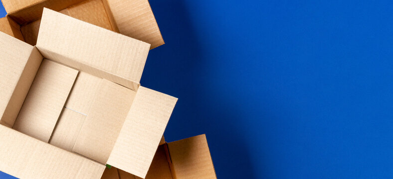 Empty open cardboard boxes on blue background. Top view