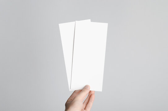 DL Flyer Mock-Up - Male hands holding blank flyers on a gray background.