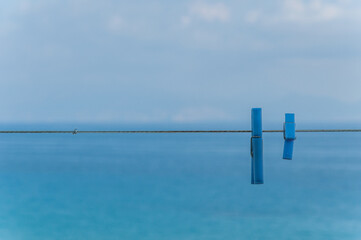 Pair of clothespins hanging from a thread, with the sea in the background
