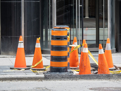 Large and small orange traffic and construction cones on a city sidewalk with yellow caution tape