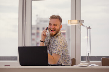 one young man, crazy laughing while talking on a phone, looking at camera.