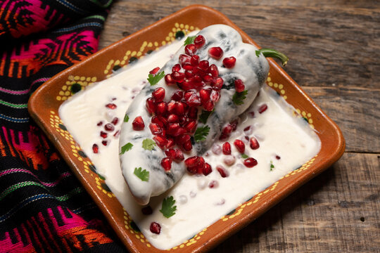 Mexican stuffed poblano peppers also called nogada with pomegranate on wooden background