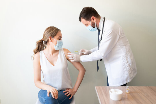Nervous woman getting a vaccine on her arm