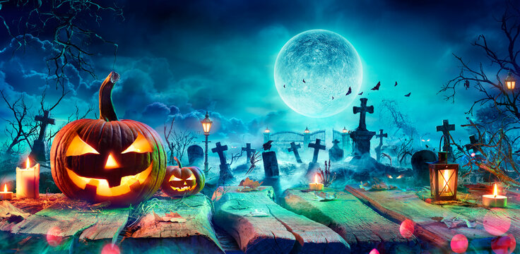 Jack O' Lantern On Table In Spooky Graveyard At Night - Halloween With Full Moon