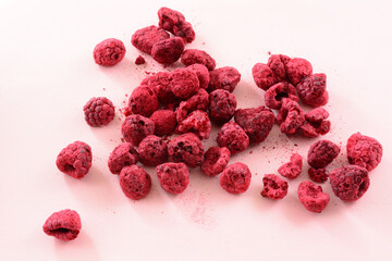 Pile of freeze dried red raspberries fruit on pink background