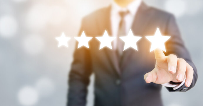 Hand of businessman touching five star symbol to increase rating of company concept
