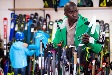 Young cheerful positive African American skier choosing ski poles in sport goods store