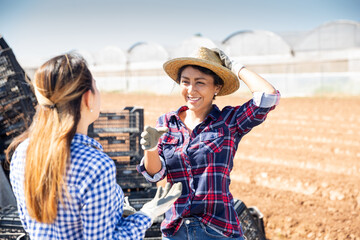 Cheerful Peruvian middle aged woman farmer talking to young workwoman near heap of plastix boxes on farm field