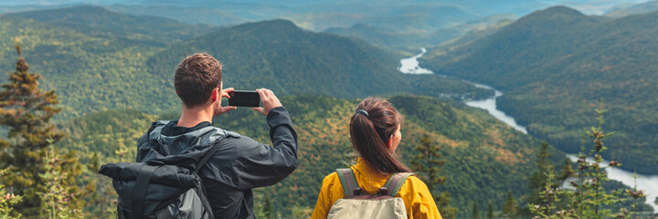 Hikers couple camping walking with backpacks in Quebec taking picture of view with phone in Autumn. Canada forest travel lifestyle banner. Tourists looking at Jacques Cartier National Park.