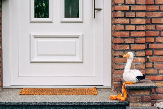Baby announcement - Front door with white stork sitting on doorstep