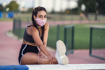 View of a young Caucasian female wearing a mask exercising on the sport field
