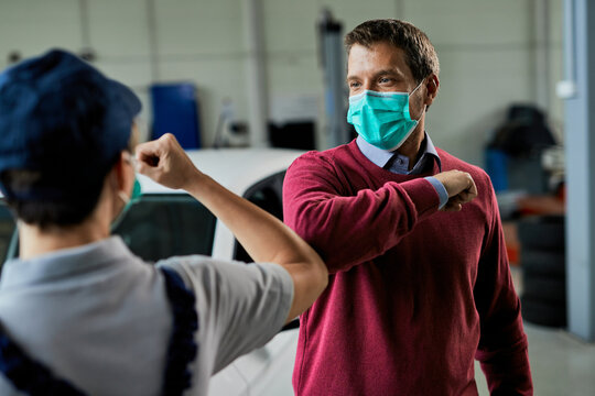 Male customer with face mask elbow bumping with female auto mechanic in a workshop.