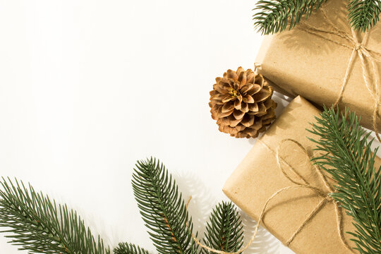 fir branches with pine cones and gifts in craft paper and scourge on a white background for text for the holiday christmas or new year