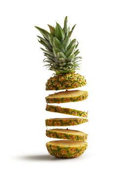 Fresh pineapple cut into slices flying, isolated from the white background