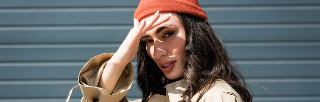 panoramic crop of stylish woman in beanie hat hiding from sunshine