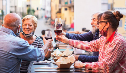 Group of old people eating and drinking outdoor - Doubble date with facemask on - Focusing glasses