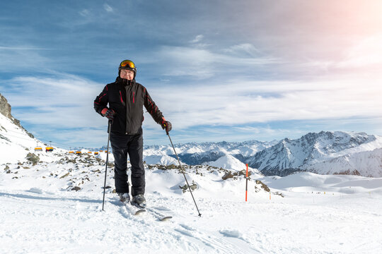 Active senior experienced mature old person in ski helmet, goggles and black suit stand on mountain peak enjoy winter extreme sport activities. Man on stunning panoramic mountains sunshine background