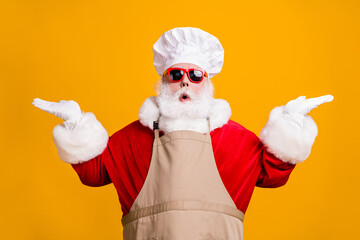 Photo of amazed santa claus with beard in chef cap hold hand compare x-mas christmas newyear magic cook meal discounts wear apron isolated bright shine color background