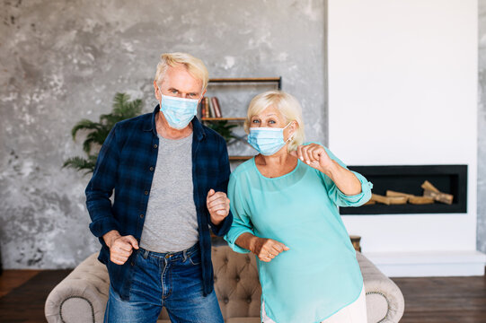 Elderly spouses wearing protective medical masks spend leisure time during quarantine with dance at home. Senior husband and senior wife are dancing in the living room