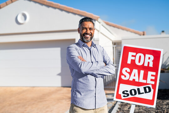 Hispanic real estate agent standing near sold sign outside house