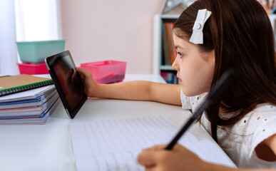 Girl doing homework with the tablet sitting at a desk in her bedroom