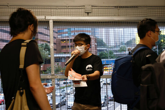 Pro-democracy activist Joshua Wong distributes leaflets encouraging people to send postcards to twelve Hong Kong residents being held in the Chinese mainland after attempting to flee to Taiwan, in Hong Kong