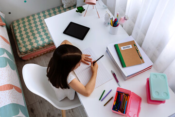 Top view of unrecognizable girl doing homework sitting at a desk in her bedroom