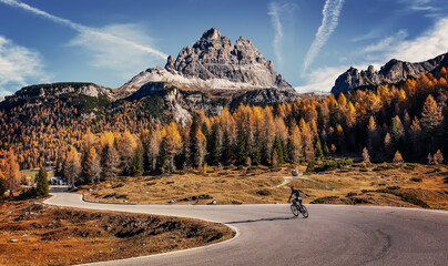 Amazing mountain landscape at autumn sunny day. scenic alpine scenery of Dolomites Alps. Wonderful view on Mountain valley, forest, and asphalt road for majestic rocky peak. travel on bike concept.