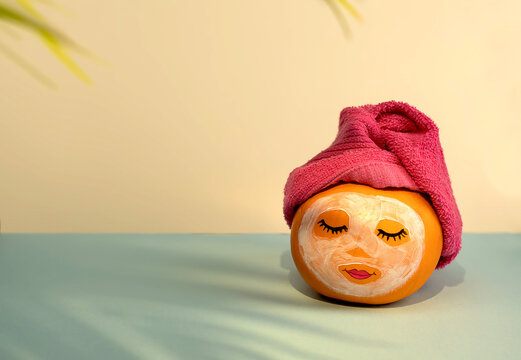 Pumpkin with painted face and facial mask, towel and flowers on pastel yellow and blue background with shadow from palm leaves. Spa concept, Helloween, Copy space.