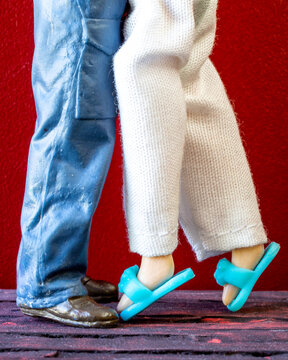 Man and woman doll legs. Man in overall and the woman in pants and blue slippers. The woman is on tip toes.