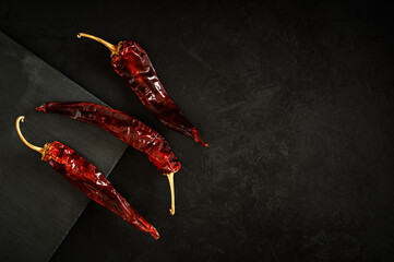 three dried red hot chili peppers lie on a background of black concrete plaster and a stone cutting board. top view. beautiful artistic dark still life with copy space