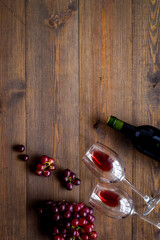 Fototapete - Red wine with grape - in glasses and bottle - on wooden desk top view copy space