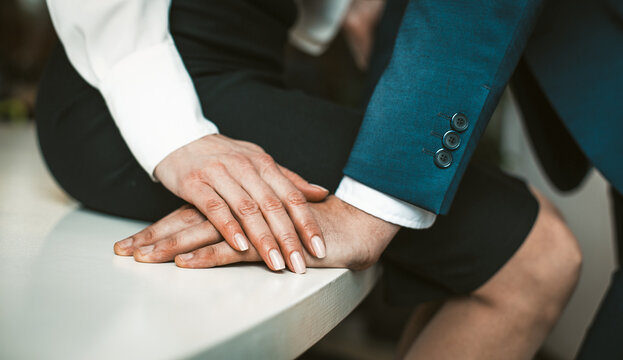 Passionate affair in the office workplace concept. Girl in a skirt sits at the edge of the table. Man stands close to her. High quality photo.