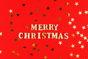 wooden letters on red background. Merry christmas lettering on red paper with scattered stars confetti. Festive greeting card.