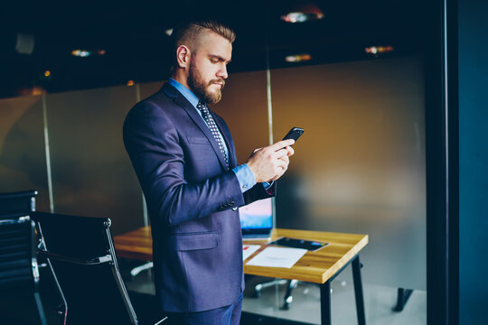 Caucasian bearded businessman 30 years old searching website for making online booking, professional trader checking received results of investment exchange and contribution to stock shares