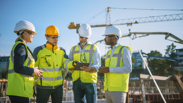 Diverse Team of Specialists Use Tablet Computer on Construction Site. Real Estate Building Project with Civil Engineer, Architect, Business Investor and General Worker Discussing Plan Details.